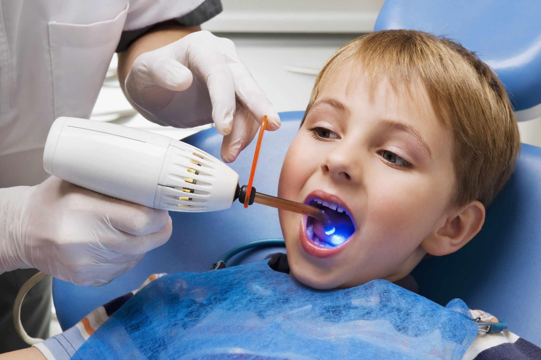 A dentist examining a boy's teeth