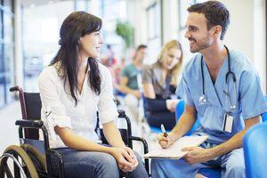 Patient in wheelchair talking to nurse in hospital