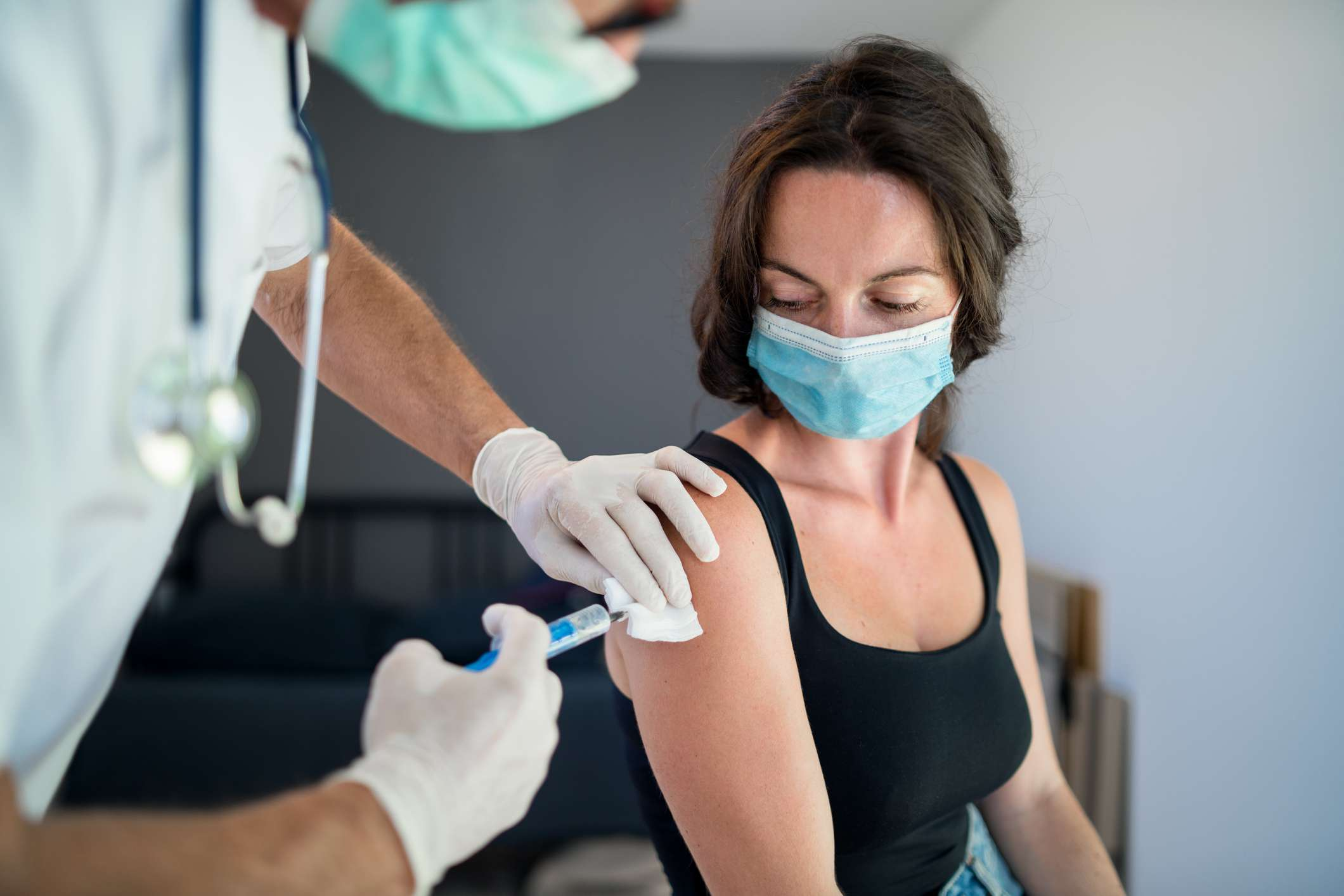 Masked woman getting COVID-19 vaccine