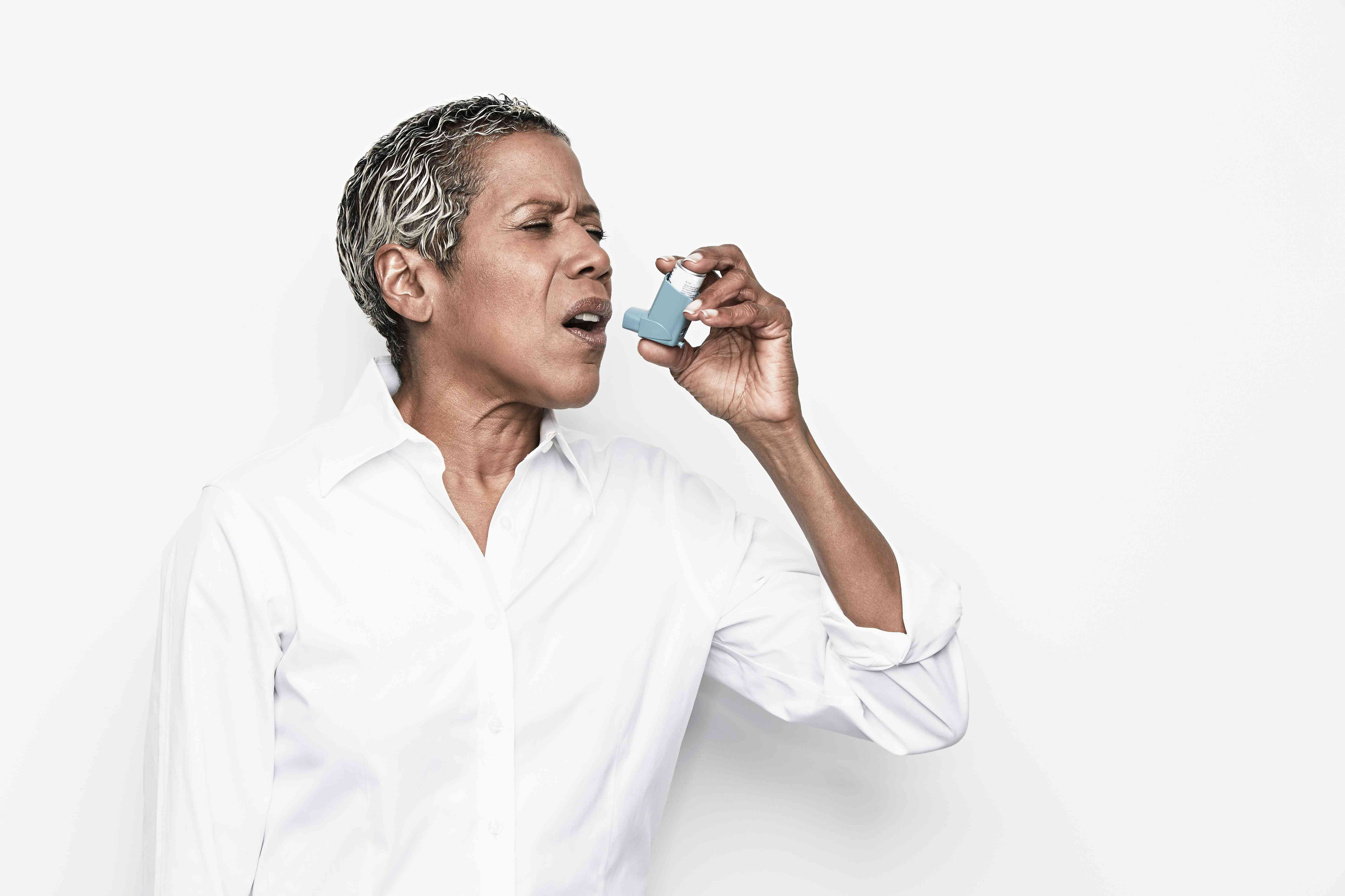 Woman in a white shirt using an inhaler standing against a white background