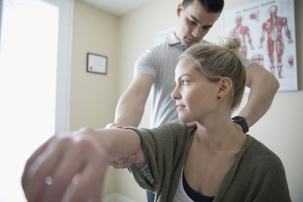 Physical therapist looking at woman's arm