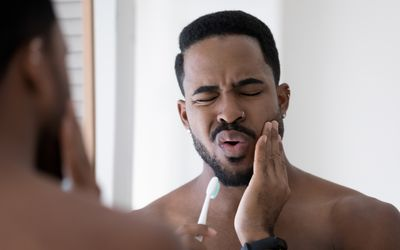 Man feeling pain and discomfort while brushing teeth in bathroom, holding toothbrush, touching cheek with painful grimace