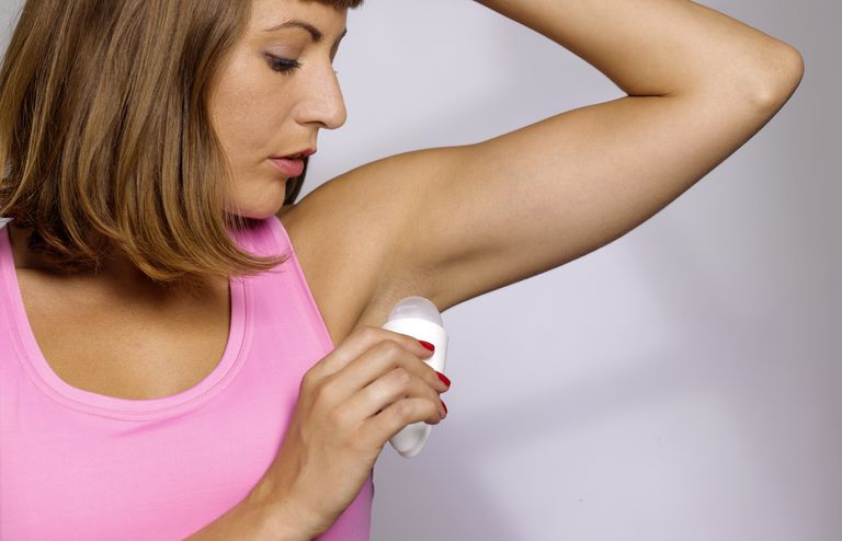 Young woman applying underarm deodorant