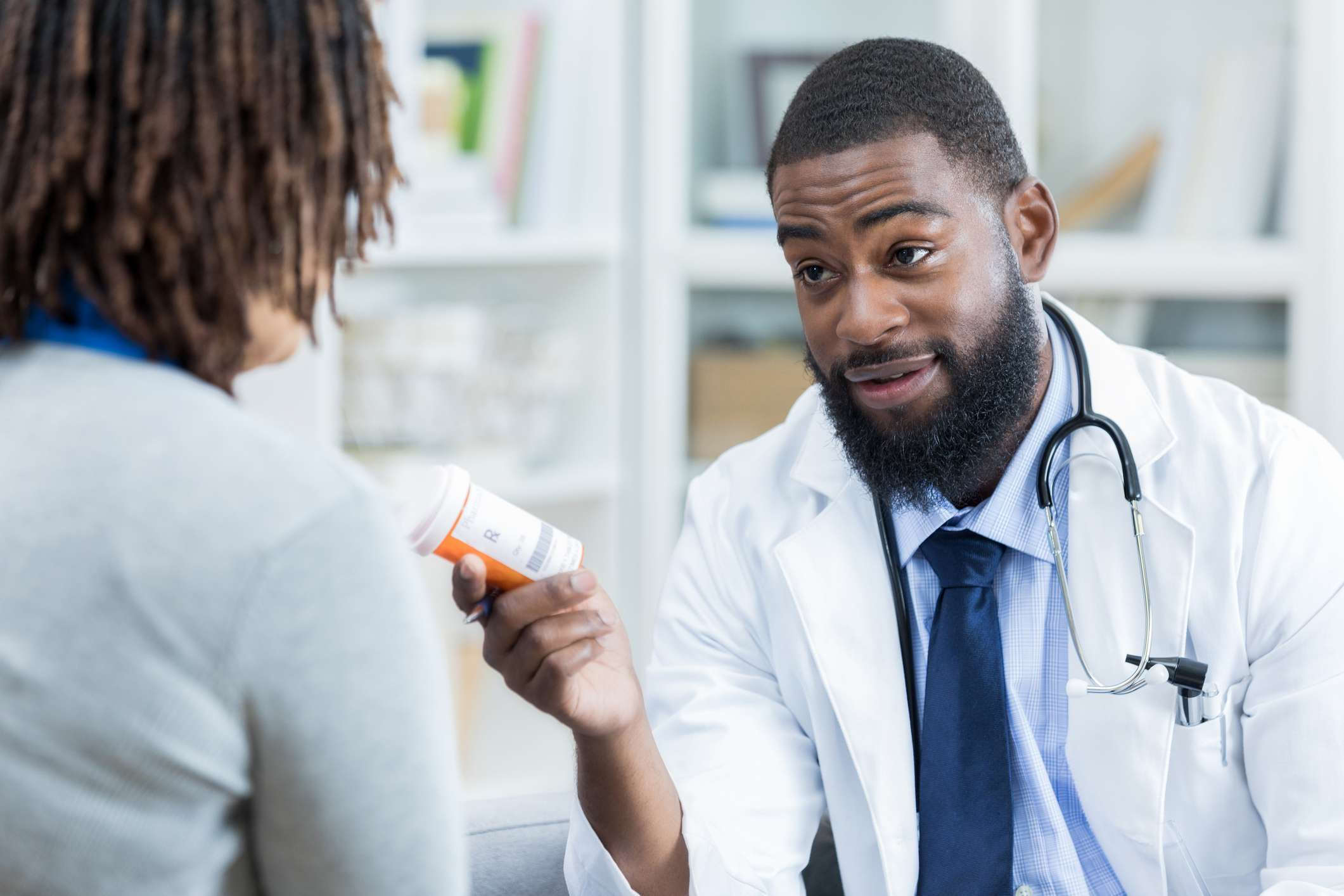 A male doctor discusses a prescription medication with a female patient. The doctor is holding the medication.