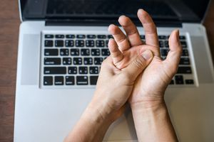 Woman holding her hand pain from using computer