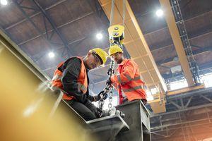 Steel workers fastening steel to crane in factory