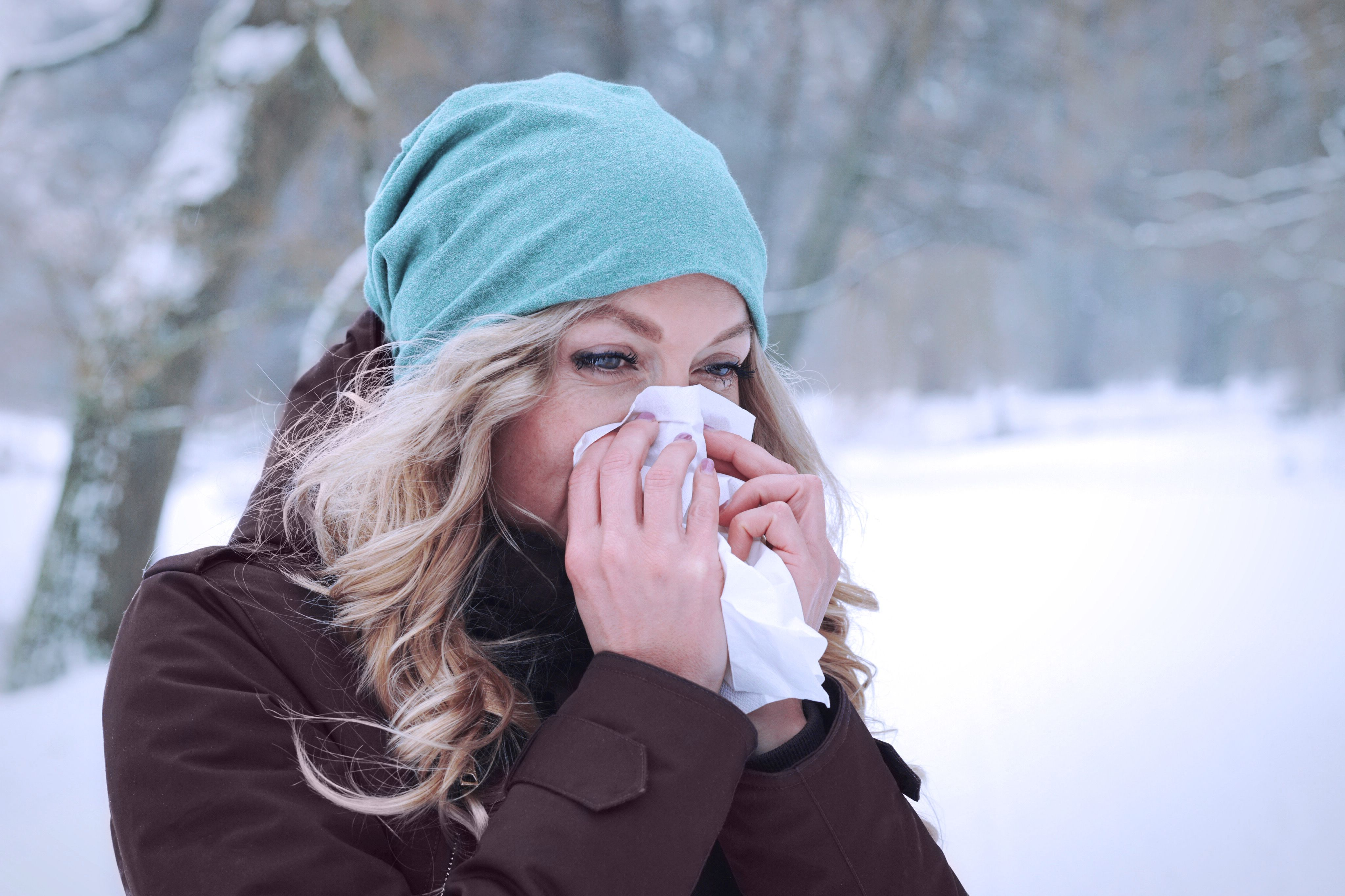 Woman blowing nose outside.
