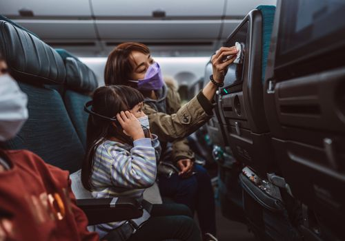 Mom and child on a flight wearing face masks.