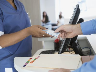 Patient giving nurse medical identification card in clinic