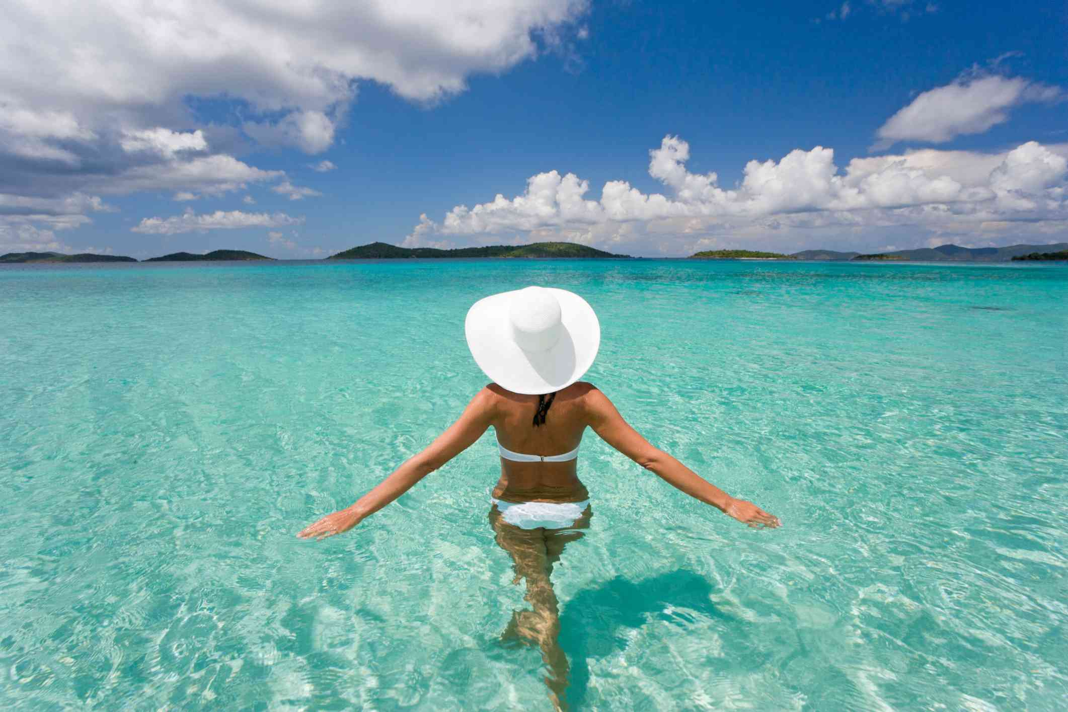 Woman in a white sun hat wading into crystal clear water