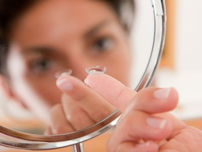 Woman with a contact lens on her finger