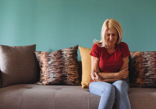 Mature woman facing pelvic pain at home.