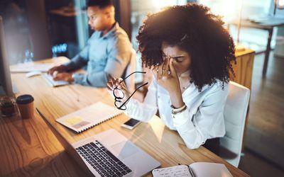 Woman pinching bridge of nose while working.