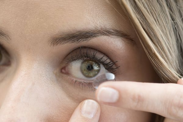 a woman putting a contact lens in her eye