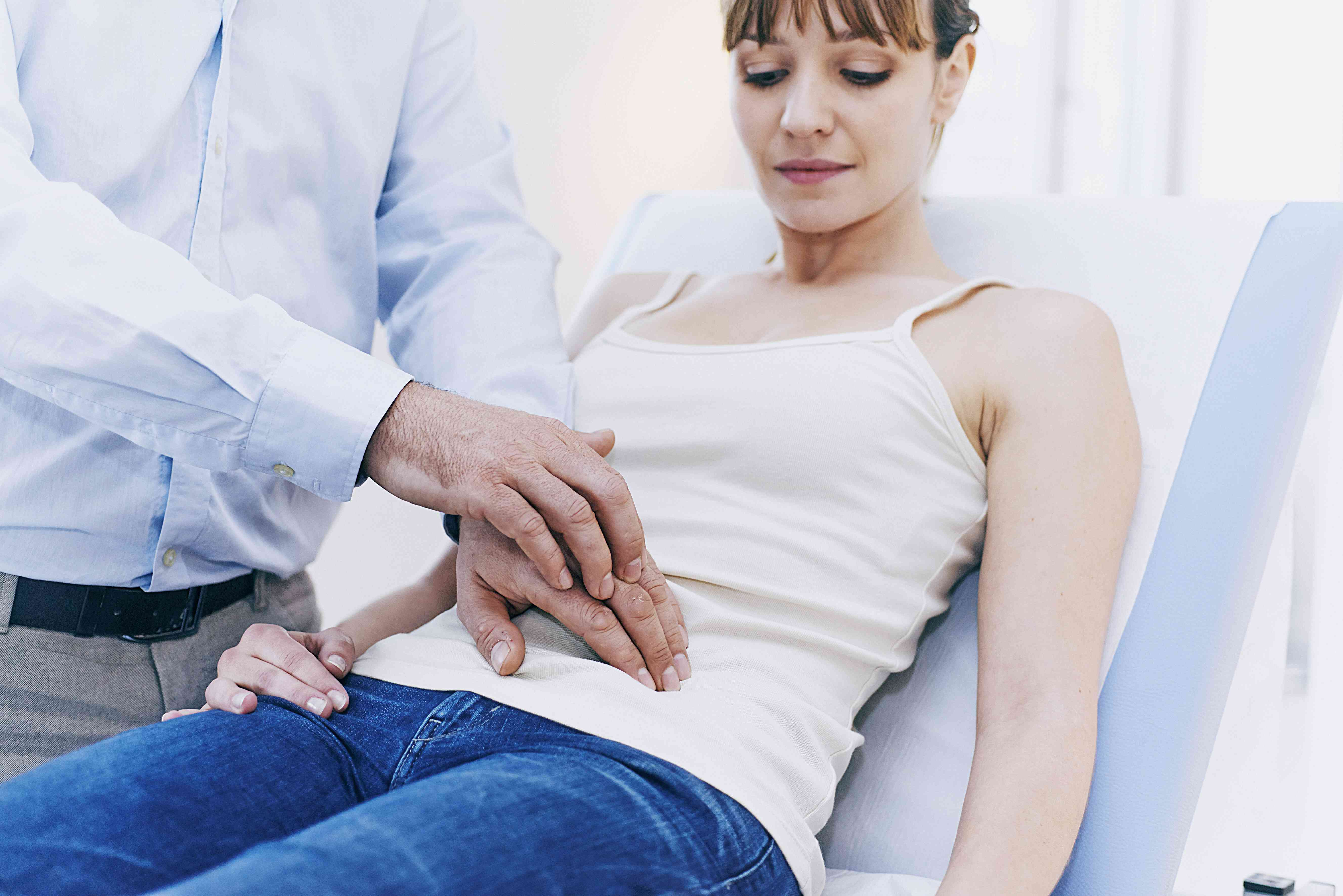 doctor examining abdomen of a patient