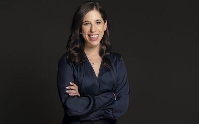 Headshot of Allara founder, Rachel Blank, on a dark background