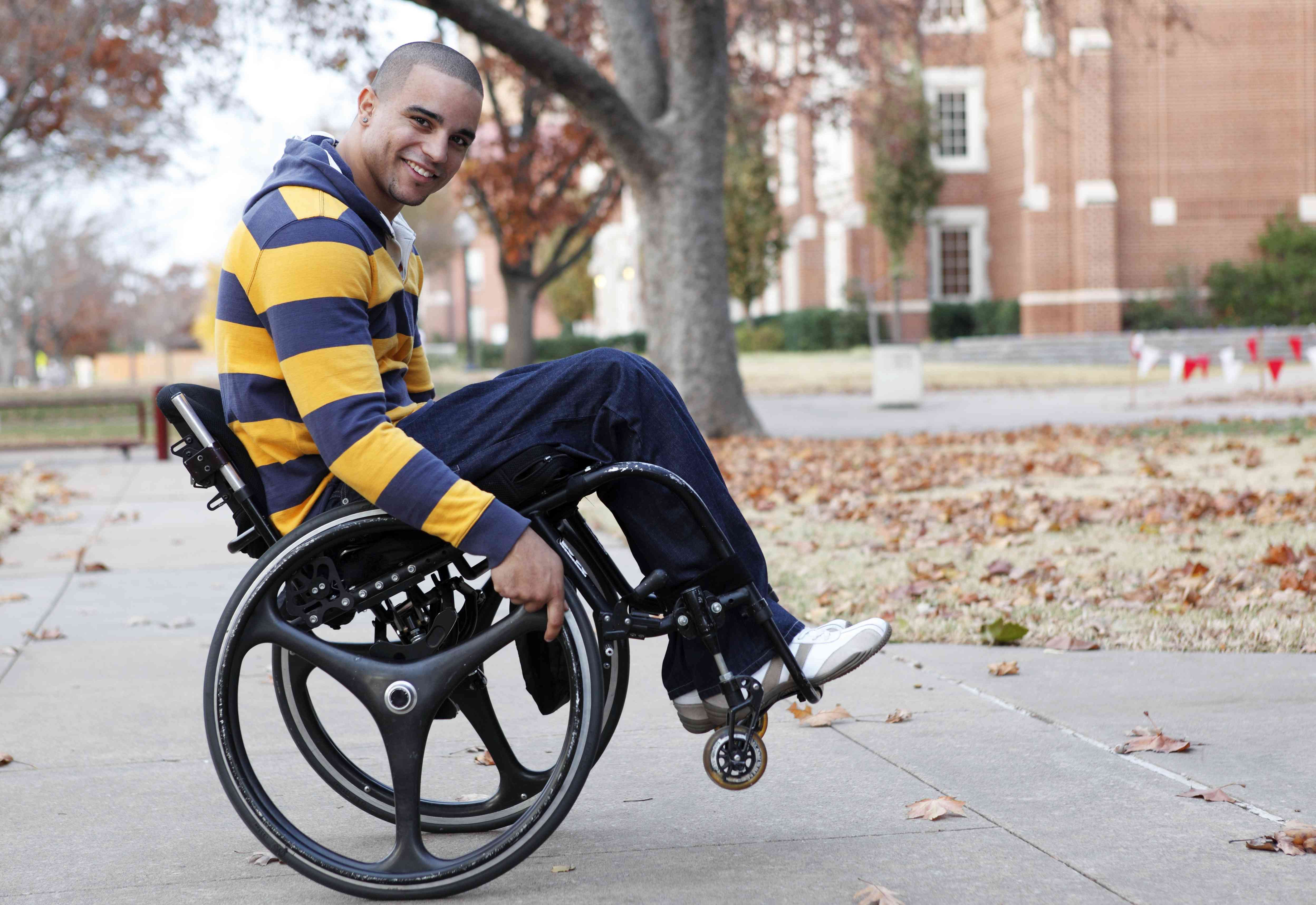 Man in wheelchair performing a wheelie and smiling at camera surrounded by a fall background