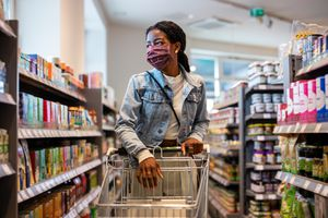 Woman grocery shopping with mask on.