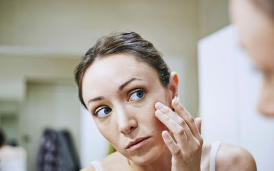 Woman looking at her face in the mirror