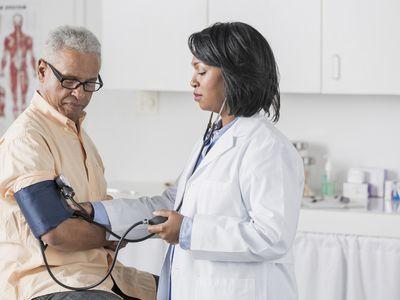 Doctor checking senior man's blood pressure