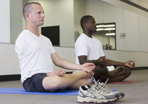 Two men doing yoga in a studio