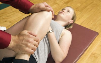 Photo of a physical therapist examining a woman's knee.