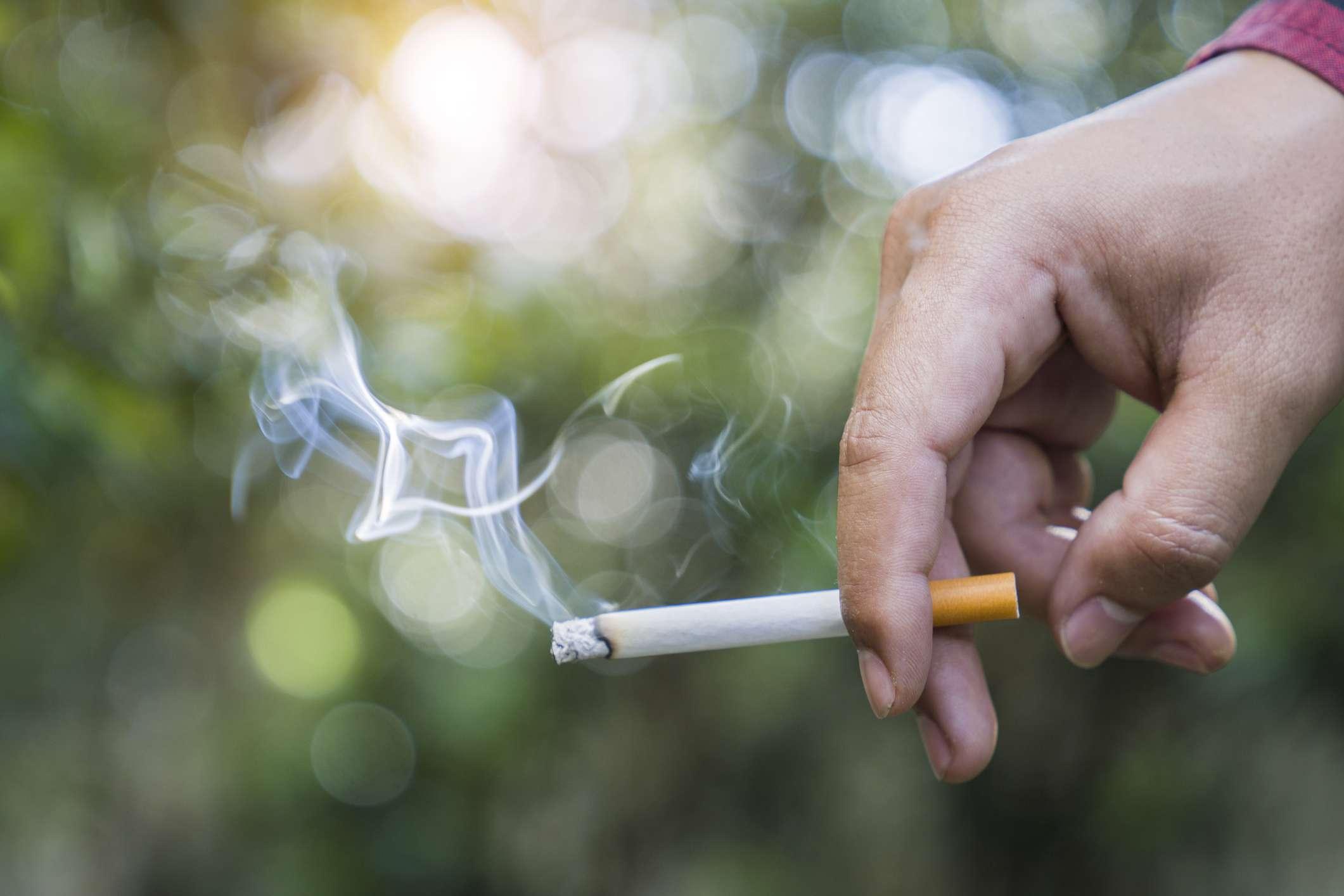 Hand holding burning cigarette