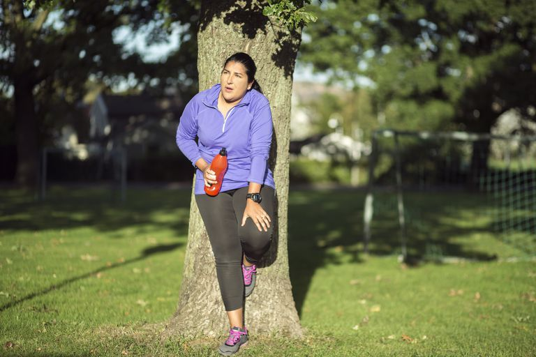 Fatigued woman leaning up against tree after workout