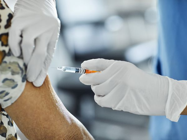 Cropped image of nurse injecting Covid-19 Vaccine to a patient. Female healthcare worker is working at hospital. She is holding syringe.