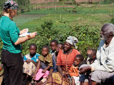 Humanitarian aid volunteer talking to villagers about malaria prevention
