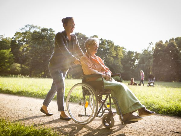 Young woman pushing an older woman in a wheelchair through a park