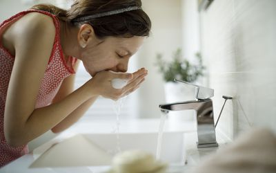 Teenage girl cleaning face with water at the sink