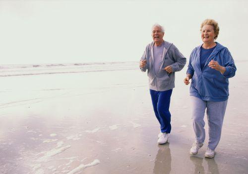 a senior couple walking on the beach