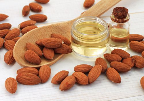 Almonds, oil or extract, and a wooden spoon