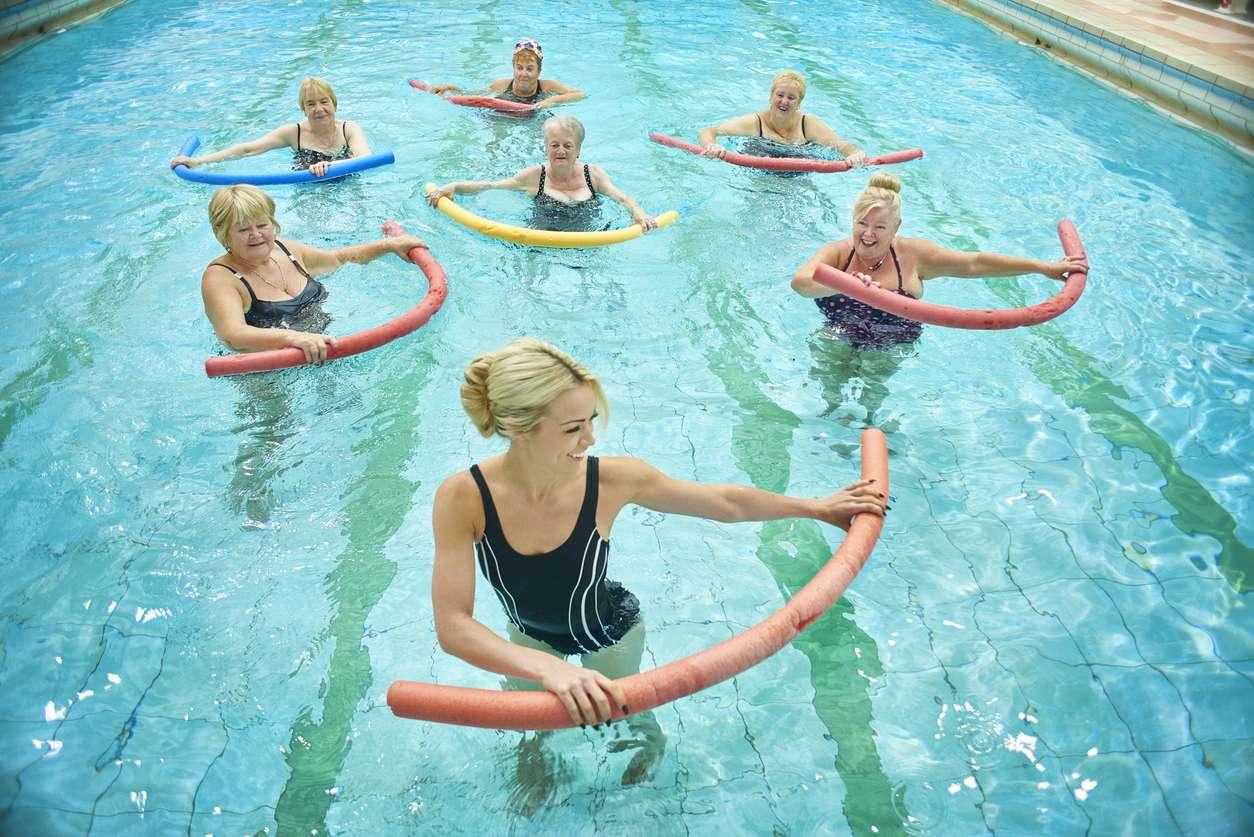 Women using fun noodles in pool