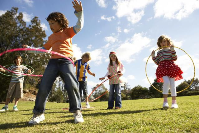 Kids playing outdoors with hula hoops