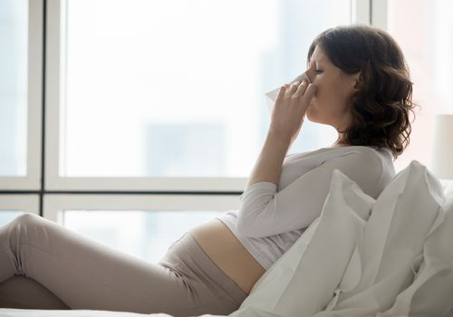 A pregnant woman sneezing into a tissue