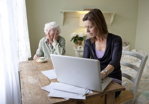 Woman reviewing bills for senior woman
