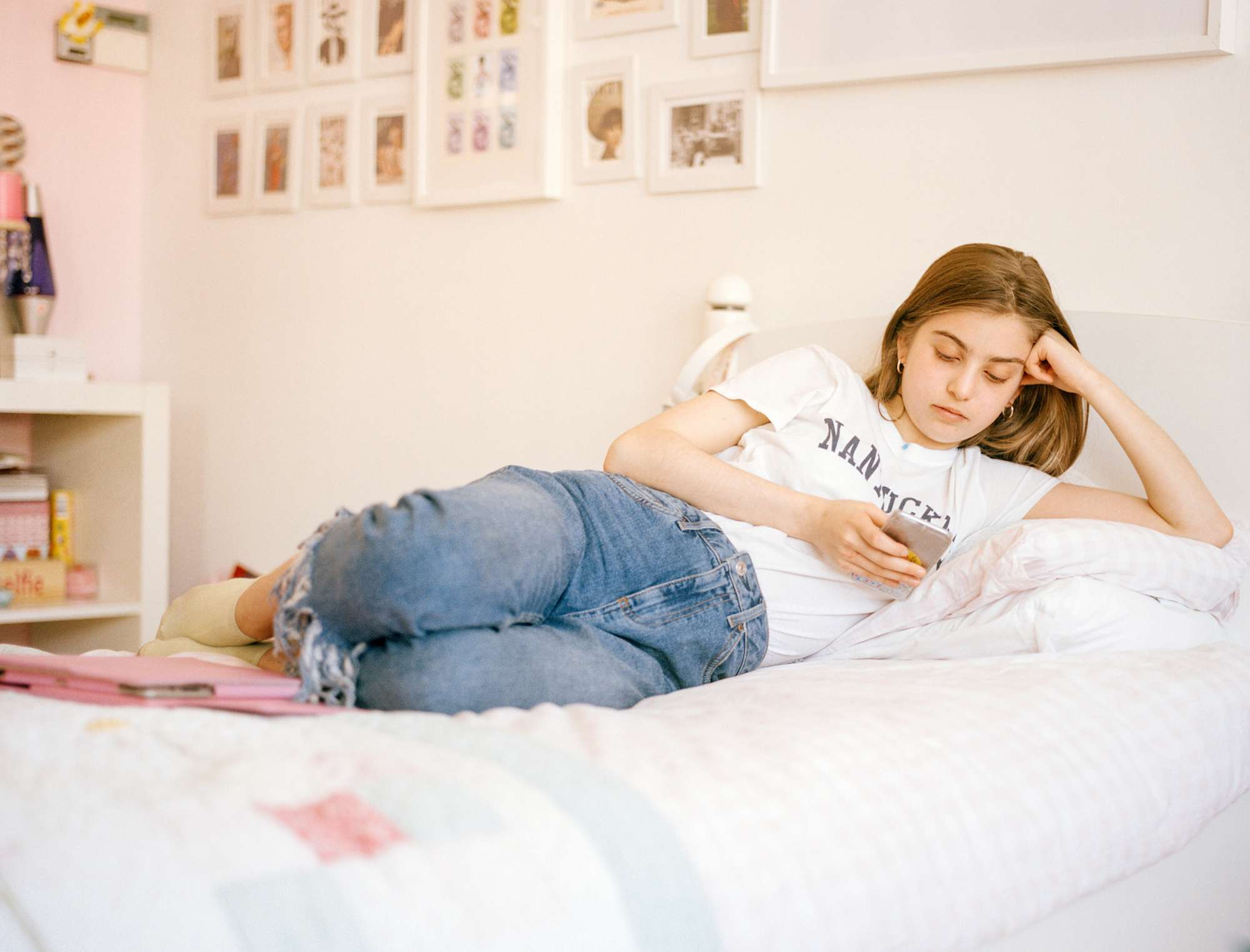 A young girl looking at her phone on her bed