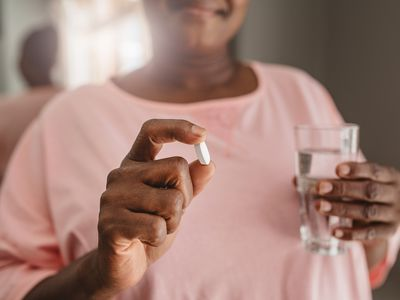 woman holding medication and glass of water