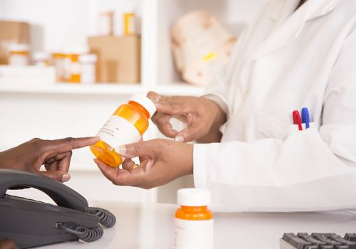Pharmacist discusses prescription with customer