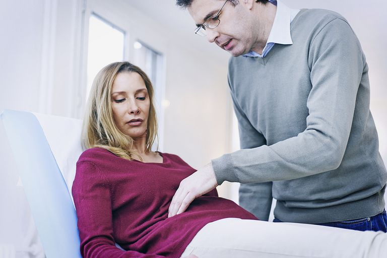 doctor evaluating woman with stomach pain