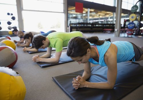 people doing plank exercise in group fitness class
