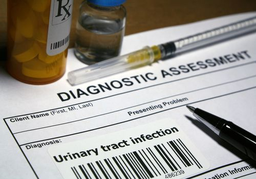 "A close up of a medical document titled ""diagnostic assessment"" with ""urinary tract infection"" as the diagnosis. There are also antibiotics next to the paper."
