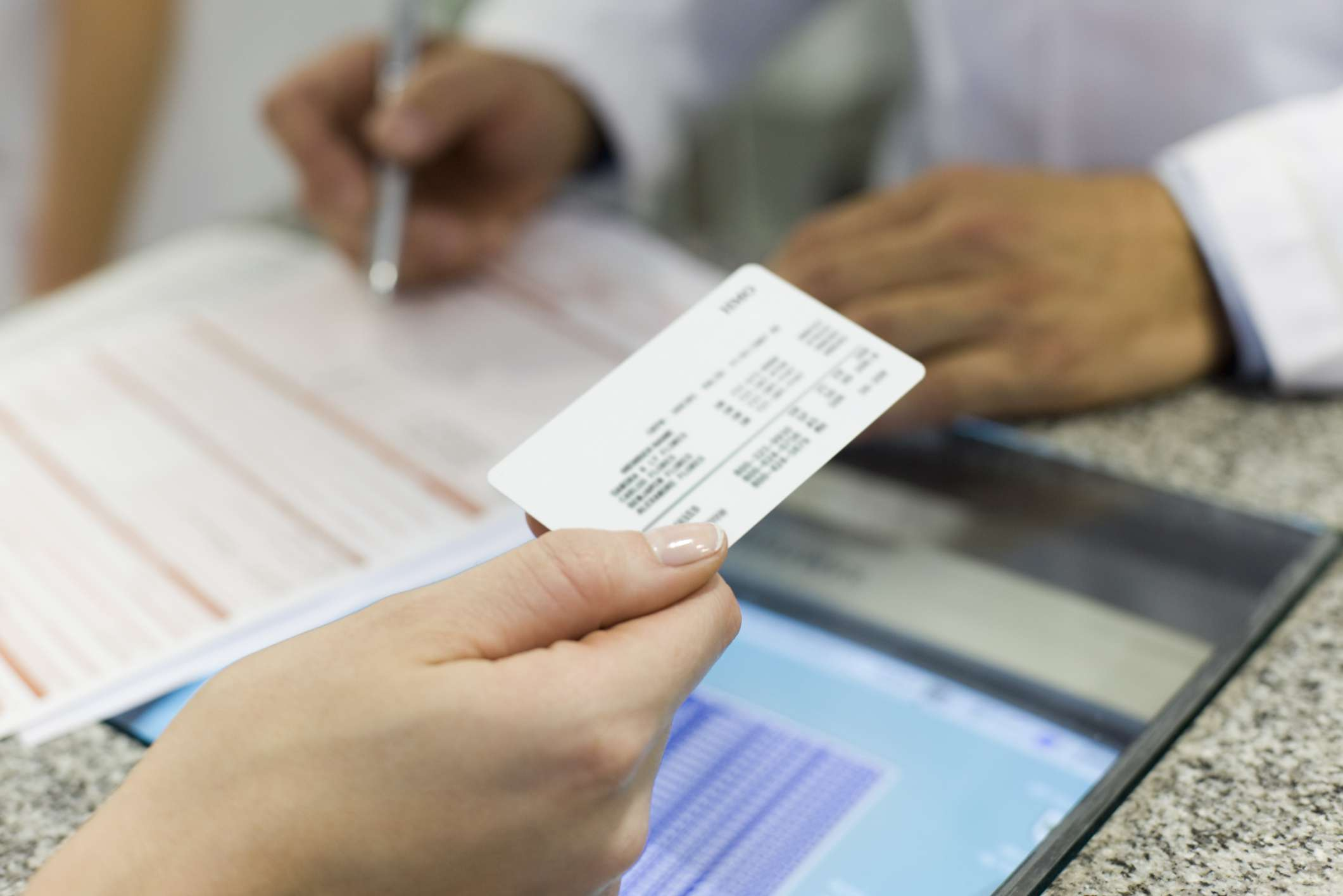 Person hanging a health insurance card to a medical receptionist
