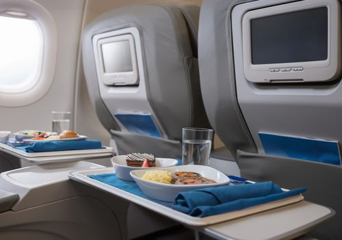 Airline meals served on seat tables.
