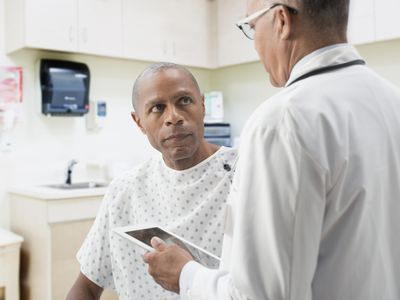 Doctor delivering diagnosis to patient in exam room