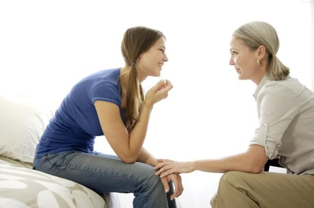 Adult woman and teenager talking against a white background