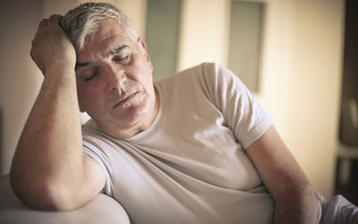 tired middle-aged man holding his head up