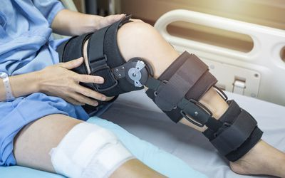 Woman in bed with a knee brace after a knee injury.